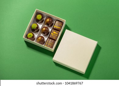 Assortment of luxury bonbons in box with copy space on green background. Exclusive handmade chocolate candy. Minimal food concept
