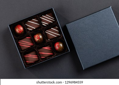 Assortment of luxury bonbons with red splashes in box on black background. Exclusive handmade chocolate candies. Copy space