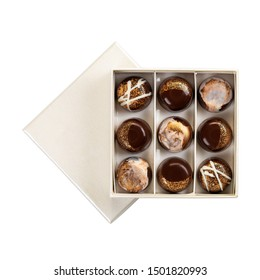 Assortment of luxury chocolate bonbons in white box isolated on white background. Gold set of exclusive handmade candies. Copy space