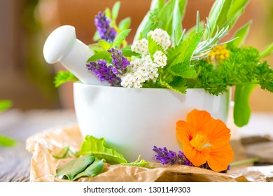 Assortment of many fresh herbs of garden such as sage, thyme, cress, laurel or lavender beautifully arranged in a mortar with copy space