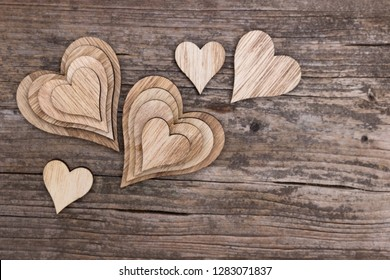 Assortment of many wooden hearts on a wooden background