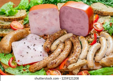 Assortment of meat products including ham and sausages with greenary and spices on wooden table closeup