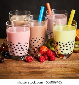 Assortment of milky bubble tea in a tea house with fresh ingredients including strawberries, raspberry , grape, chocolate, kiwi and orange