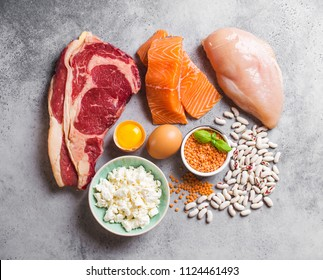 Assortment of natural sources of protein from food: meat, fish, chicken, dairy products, eggs, beans. Diet, healthy eating, wellness, bodybuilding concept, top view, stone background