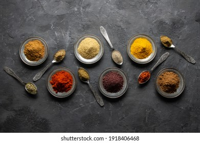 Assortment of natural spices on a vintage silver spoons or dishes on dark rustic stone background, Healthy spice concept