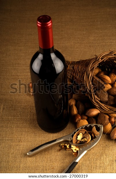 Assortment of nuts in basket with red wine bottle and nutcracker on brown background