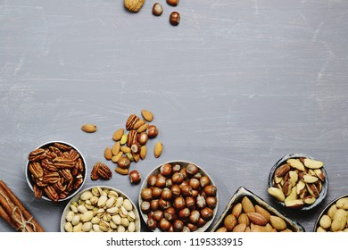 Assortment of nuts in bowls.  Hazelnuts, walnuts, pistachio, pecans, peanut, almond, brazil nuts. Food mix background, top view, copy space, banner