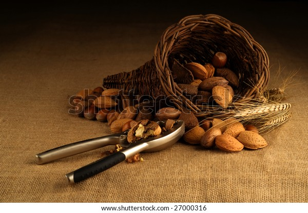 Assortment of nuts displayed in basket with nutcracker on hessian background