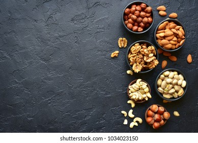 Assortment of nuts on  a black slate or stone background - healthy snack.Top view with copy space.
