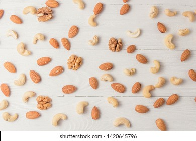 Assortment of nuts on white wooden table. Cashew, hazelnuts, walnuts, almonds. top view.