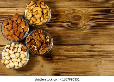 Assortment of nuts on wooden table. Almond, hazelnut, walnut and cashew in glass bowls. Top view, copy space. Healthy eating concept