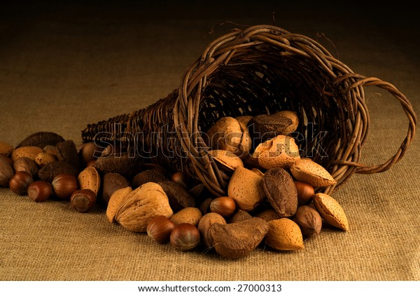 An assortment of nuts overflowing a basket on hessian background