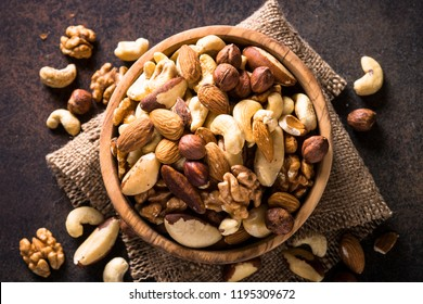 Assortment of nuts in wooden bowl on dark stone table. Cashew, hazelnuts, walnuts, almonds, brazilian nuts and pine nuts. Top view.