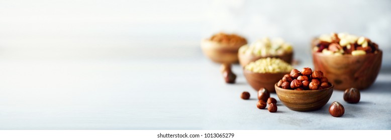 Assortment of nuts in wooden bowls. Cashew, hazelnuts, walnuts, pistachio, pecans, pine nuts, peanut, raisins. Food mix background, top view, copy space, banner
