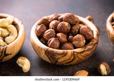 Assortment of nuts in wooden bowls. Cashew, hazelnuts,  almonds on rustic table.
