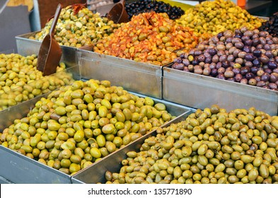 assortment of olives, pickles and salads on market stand in Israel