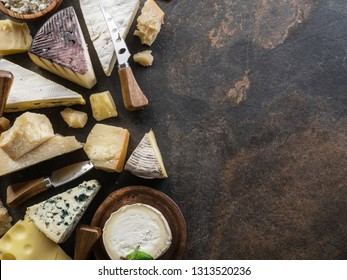 Assortment of organic cheeses on stone background. Top view. Tasty cheese starter.