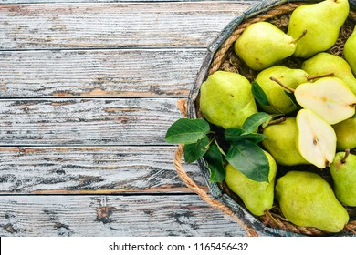 Assortment of pears in a wooden box. On a white wooden table. Free space for text. Top view.