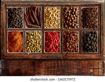 Assortment of peppers in a rustic wooden box. From left to right and from top to bottom: 1 Black 2 Long red Kampot 3 White 4 Allspice 5 Melegueta 6 Aleppo 7 Green 8 Schinus molle 9 Sichuan 10 Assam