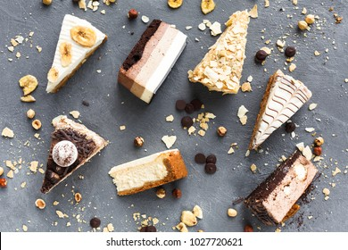 Assortment of pieces of cake on messy table, copy space. Several slices of delicious desserts, restaurant menu concept, top view
