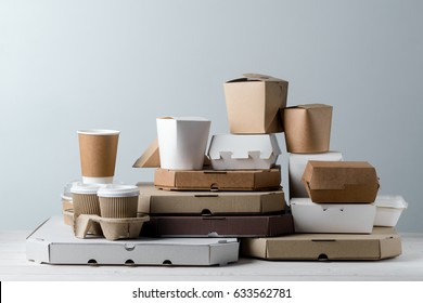 Assortment of pizza boxes, paper food containers, take-out coffee cups in holder, close-up. Light grey background, wooden surface. Food delivery.