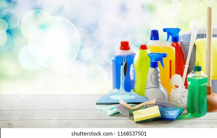 Assortment of plastic bottles with cleaning supplies together with sponges, a toilet brush, plunger and bucket on a table with high key background and copy space