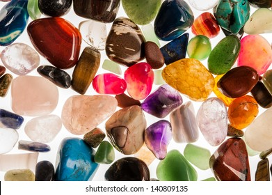 Assortment of polished semi-precious gem stones shot in the studio against white background.