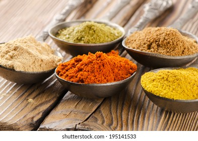 Assortment of powder spices on spoons. Selective focus