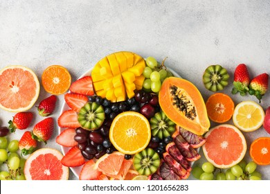Assortment of raw fruits berries, mango, oranges, kiwi strawberries, blueberries grapefruit grapes, bananas apples on the white plate, on the off white table, top view, copy space
