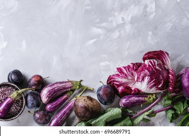 Assortment raw organic of purple vegetables mini eggplants, spring onion, beetroot, radicchio salad, plums, kohlrabi, flower salt over gray concrete background. Top view with space. Food frame