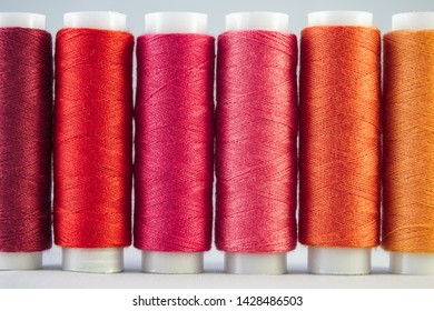 An assortment of red sewing threads on white background