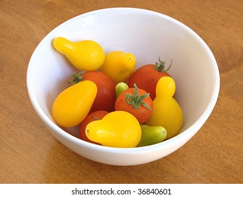 Assortment of red, yellow, and green tomatoes in a white bowl