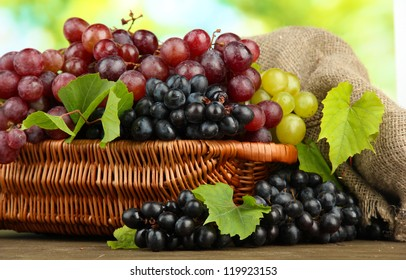 assortment of ripe sweet grapes in basket, on green background