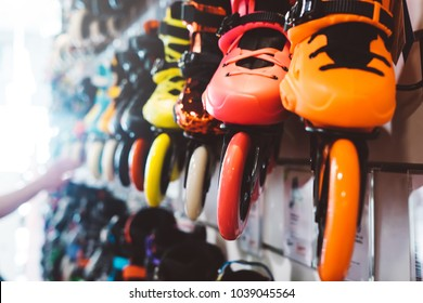 Assortment roller skates isolated in store shop, person choosing and buy color roller-skates on backgraund sun flare, healthy lifestyle concept close up, man consider sport footwear for rollerblade