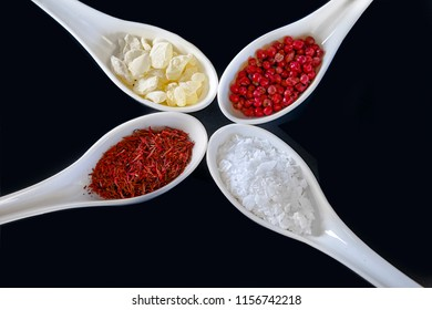 An assortment of  saffron, mastika, pink peppercorns and salt flakes  in white spoons. Stock Image.