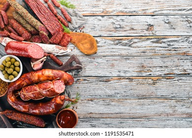 Assortment of salami and snacks. Sausage Fouet, sausages, salami, paperoni. On a white wooden background. Top view. Free space for your text.