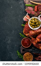 Assortment of salami and snacks. Sausage Fouet, sausages, salami, paperoni. On a stone background. Top view. Free space for your text.