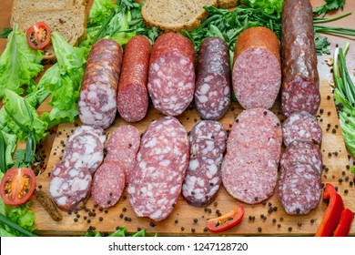Assortment of salami and snacks. Sausages, salami, paperoni with spices and vegetables