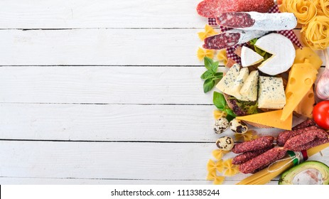 Assortment of sausage, cheese and fresh vegetables. On a white wooden background. Top view. Copy space.