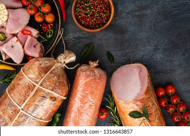 Assortment of Sausage and ham . Assorted meat products, including smoked sausages and ham with vegetables and spices. Copyspace. Top view.