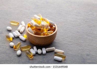 Assortment scattered pharmaceutical medicine vitamins, pills, drugs in wooden bowl on gray background. White food dietary supplement hard shelled capsules filled with powder, fish oil softgel Omega 3