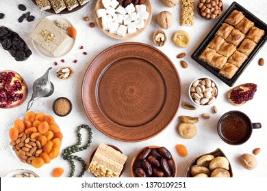 Assortment, set of Eastern, Arabic, Turkish sweets, nuts and dried fruits around plate, top view, copy space. Holiday Middle Eastern traditional sweet food.