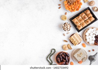 Assortment, set of Eastern, Arabic, Turkish sweets, nuts and dried fruits on white table, top view, copy space. Holiday Middle Eastern traditional sweet food.