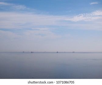 An assortment of ships out in the ocean can be seen along the horizon, through a misty afternoon atmosphere.