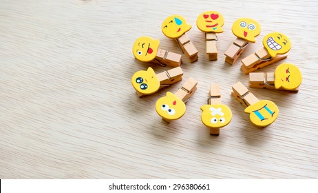 Assortment of smiley faces emoticon on clothes peg on wooden surface. Concept of emotions or meta communicative pictorial representation of a facial expression. Slightly de-focused. Copy space.