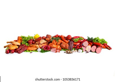 Assortment of smoked products. Decorated with vegetables and leaves of green salad. Composition from different kinds of sausage. Isolated on white background