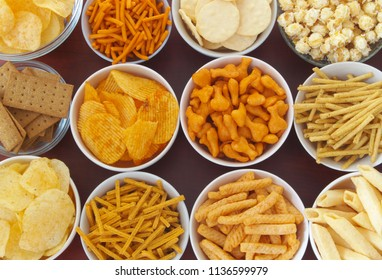 Assortment of snackes on wooden table, crackers, chips, sticks, cookies