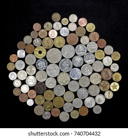 Assortment of South American and West Atlantic area coins, various denominations. Many different interesting designs on black background.