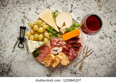 Assortment of spanish tapas or italian antipasti with meat, ham, olives, cheese, nuts and bread placed on a white rusty table. Top view flat lay with copy space background