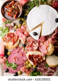 Assortment of spanish tapas or italian antipasti (jamon, prosciutto, chorizo, salami) on a wodden board (rustic style). top view .